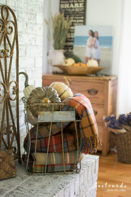 vintage wire egg crate with faux pumpkins and plaid throw blankets