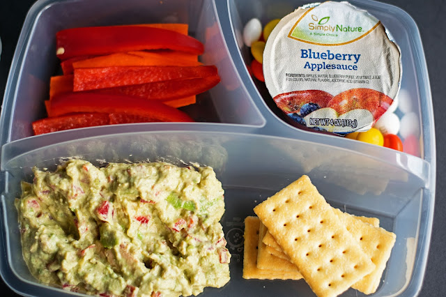A picture of the lunch box with the tuna salad, crackers, carrot sticks, and apple sauce.