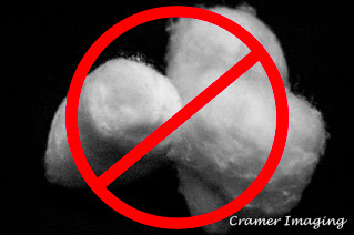 Photograph of white cotton balls and a don't use sign in red on black background by Cramer Imaging