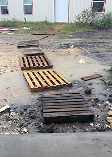 Used pallets in the mud make an unstable sidewalk.