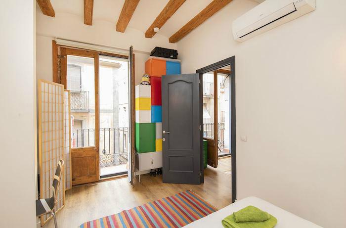 Almacenaje secundario en un dormitorio pequeño con split de aire acondicionado