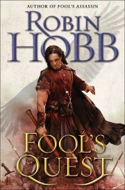 Cover of Fool's Quest, featuring a dark-haired white man in medievalesque leather armour. He wields an ax. Ghostly, feathered wings rise above his shoulders.