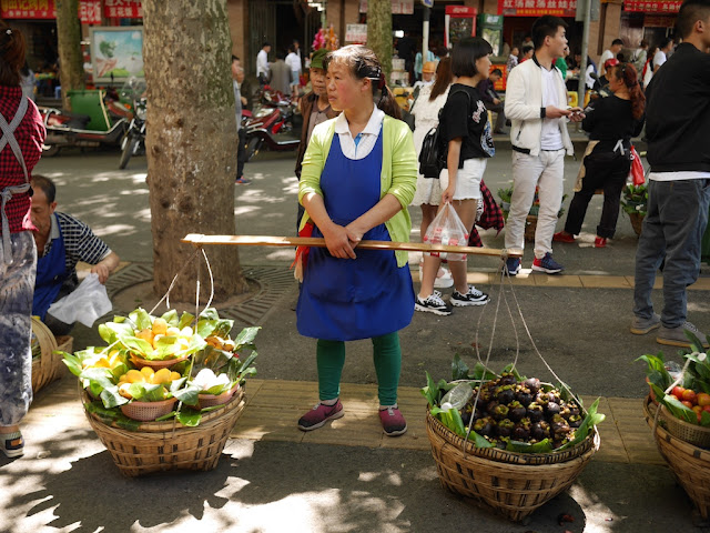 woman selling mangos and mangosteens alongside a street in Guiyang