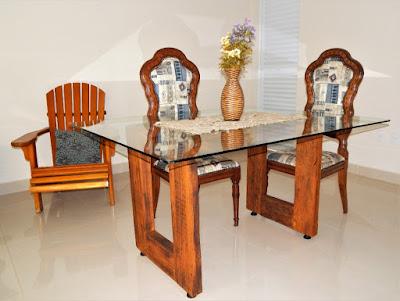 Esta mesa foi concebida pelo próprio Manzan. Ela usa vigas de peroba, oriundas de um telhado de mais de 40 anos, sob um tampo de vidro temperado. A simplicidade e a beleza para decorar o ambiente da churrasqueira.