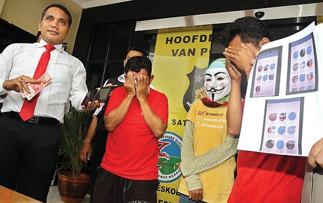 Kasatreskrim Polrestabes Surabaya AKBP Shinto Silitonga (kiri) menunjukkan barang bukti handphone yang dipakai tersangka Sugianto untuk mencari partner gangbang.
