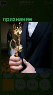 в руках мужчины статуэтка в знак признания его успехов