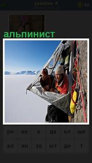 Два альпиниста в палатке висят на скале с креплением и веревками