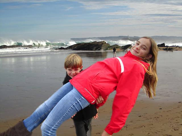 Foto trucada simulando un hijo muy fuerte que coge en brazos a su hermana mayor