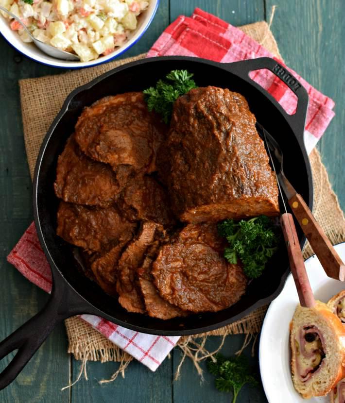 Pieza de carne completa y en porciones, servida sobre una sartén y acompañada con ensalada cocina y pan de jamón
