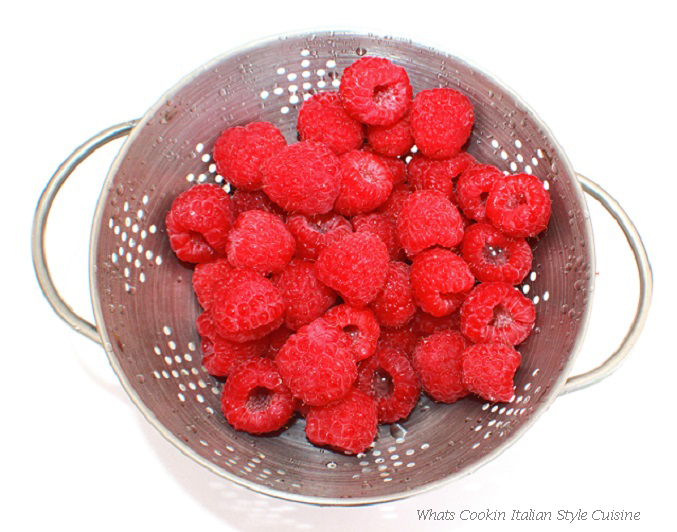 this is a colander full of fresh red raspberries