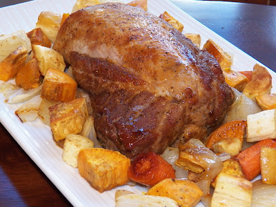 whole pork roast surrounded by vegetables