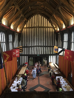 Photograph of Great Hall of Gainsborough Old Hall, imposing room with half timbered walls, vaulted wood ceiling and banners hanging from the walls