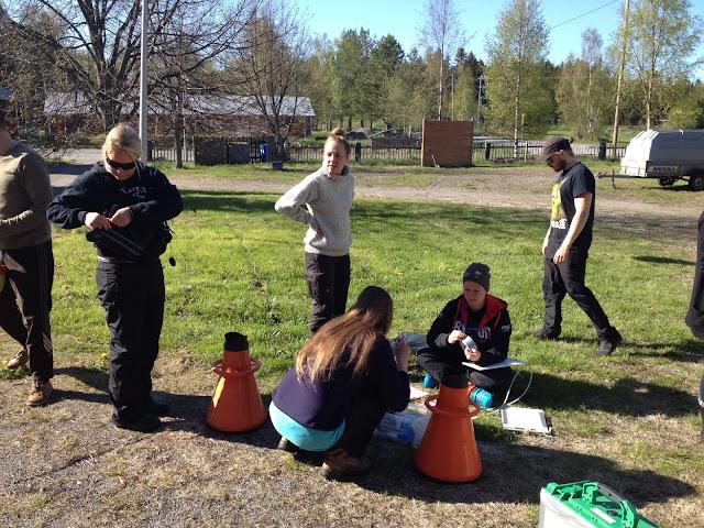 Henkilöitä ja vesikiikareita nurmikolla