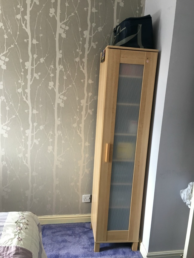 Bedroom-makeover-with-Valspar-Paint-before-image-of-bed-cupboard-and-wallpapered-wall