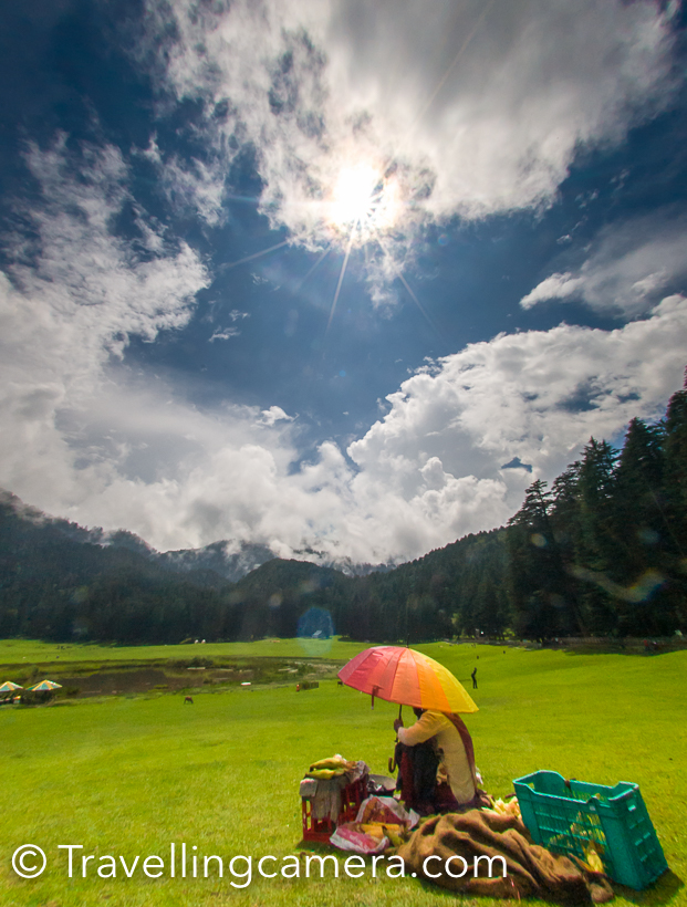 A visit in an year to Khajjiar  has made me click less photographs and rather experience different weather there. I was in Khajjiar during monsoons and this is probably the best season to experience lush green landscapes all around. Khajjiar, at times, is not accessible during winters because roads get closed due to snowfallThis is the first view of Khajjiar lake when you are coming from Dalhousie. This is the point where you should start looking for parking slot. Road condition is usually not very good during monsoons. Maintaining roads in hills is very challenging, but still Himachal has been aggressive in maintaining it's roads. Especially roads in tourist regions.During Monsoons, it's very important to keep umbrella with you, even if sun is shining and there is no patch of clouds. This change in minutes and hence very unpredictable. Our day started with clear sky and by the time we reached Khajjiar it started raining heavily. Fortunately we were carrying few umbrellas and borrowed one from our cab driver.While it was raining, we took a table in one of the restaurants around Khajjiar Lake. It was lunch time and we thought of utilizing this time and had lunch. I am forgetting the name of the place where we had lunch and it was good Punjabi food.A few kilometers ahead there is a temple with this huge Shiva idol. Now let me share a very useful tip. If you came to Khajjiar from Dalhousie in a bus and want to go back in bus only. Reach this place 30 minutes back. Usually there are lot of folks who board bus in Khajjiar and it becomes very challenging to get in. Since this temple is a stop before Khajjiar, there is good probability to get in comfortably and also find a seat. There are 2 buses from Khajjiar to Dalhousie between 1pm to 3pm.So if you come early in the morning, the timings would suit you.These days paragliding  is also quite popular activity around Khajjiar. One flies from a surrounding hill. You need to climb of the hill, so be sure about it. After flight