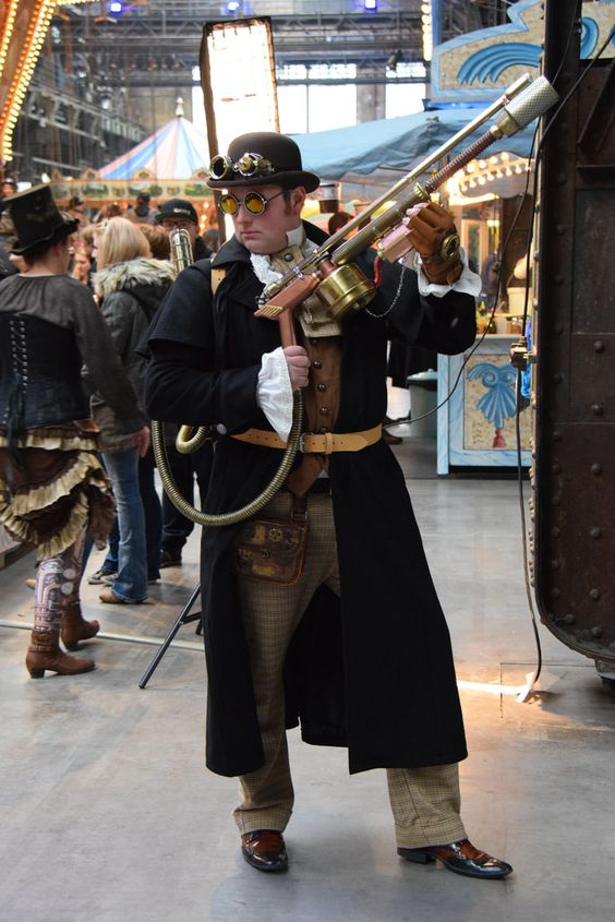 Man wearing steampunk clothing (goggles, hat, vest, pants, coat, ascot) and carrying a steampunk pump action shotgun with backpack