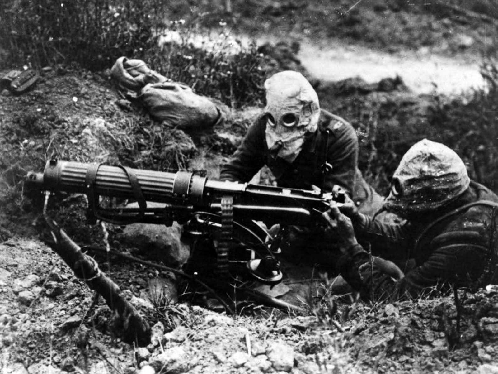 Hombres con máscara de gas del cuerpo de ametralladoras británico con una ametralladora Vickers.