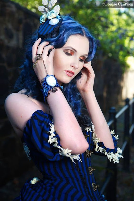 Steampunk woman in black and blue striped corset/dress. She has blue hair and bronze/copper eyshadow, blue gothic jewelry, and a blue fascinator. Subtle beautiful makeup.