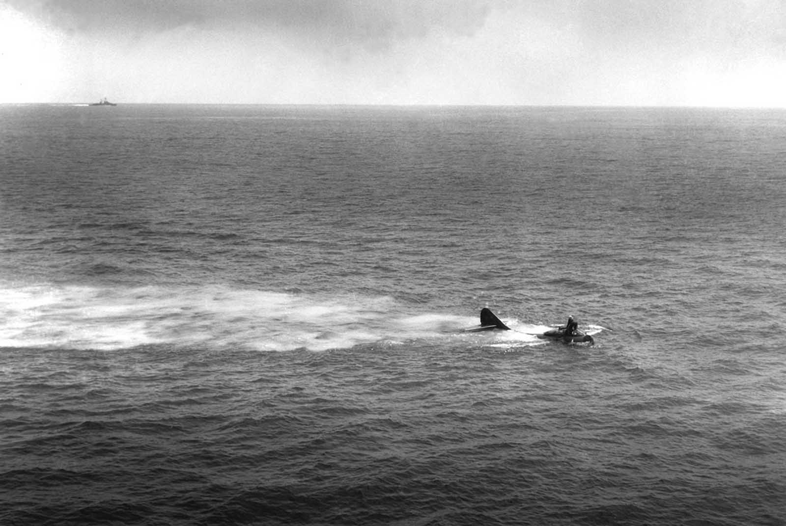 F9F-2 floating on water after crash over bow of USS Philippine Sea (CV-47) near Korea. Cdr. R. Weymouth stands on the nose of the plane awaiting rescue.