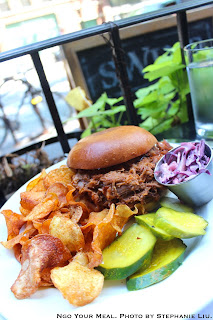 Pulled Pork Sandwich with mango bourbon chipotle sauce, red Cabbage slaw, pickles at Swine