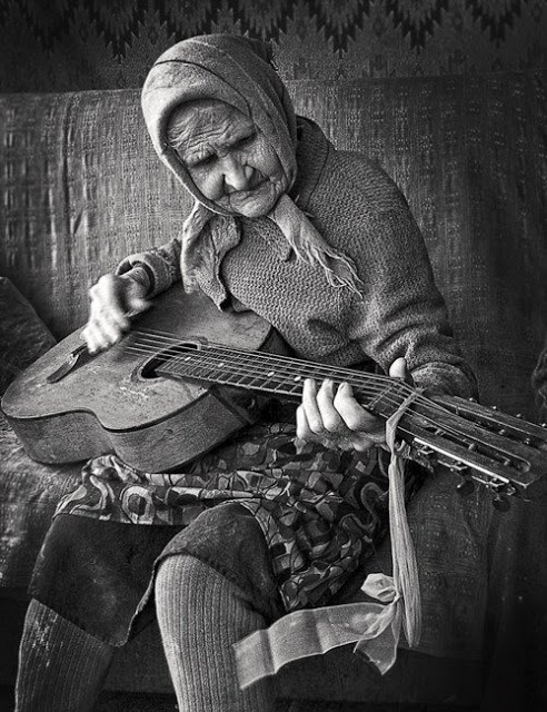 Beautiful black and white photo of old lady wearing layers of clothes and playing the guitar