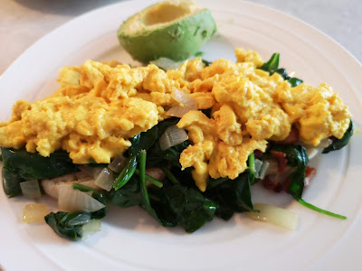 Scrambled eggs on a bed of spinach and a toasted English Muffin