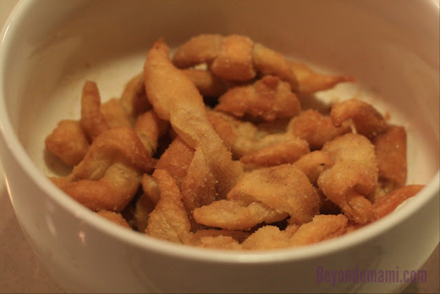 Bowl of left-over puff pastry scraps deep-fried and sprinkled with sugar.