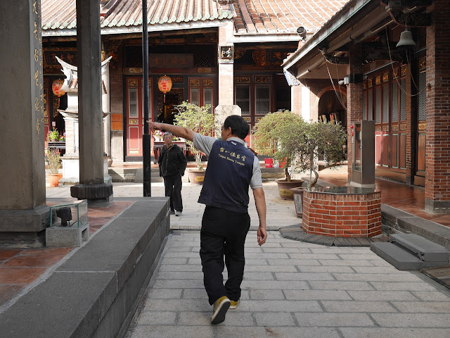 "Man wearing ""Taipei Baoan Temple"" pointing a man in the right direction"