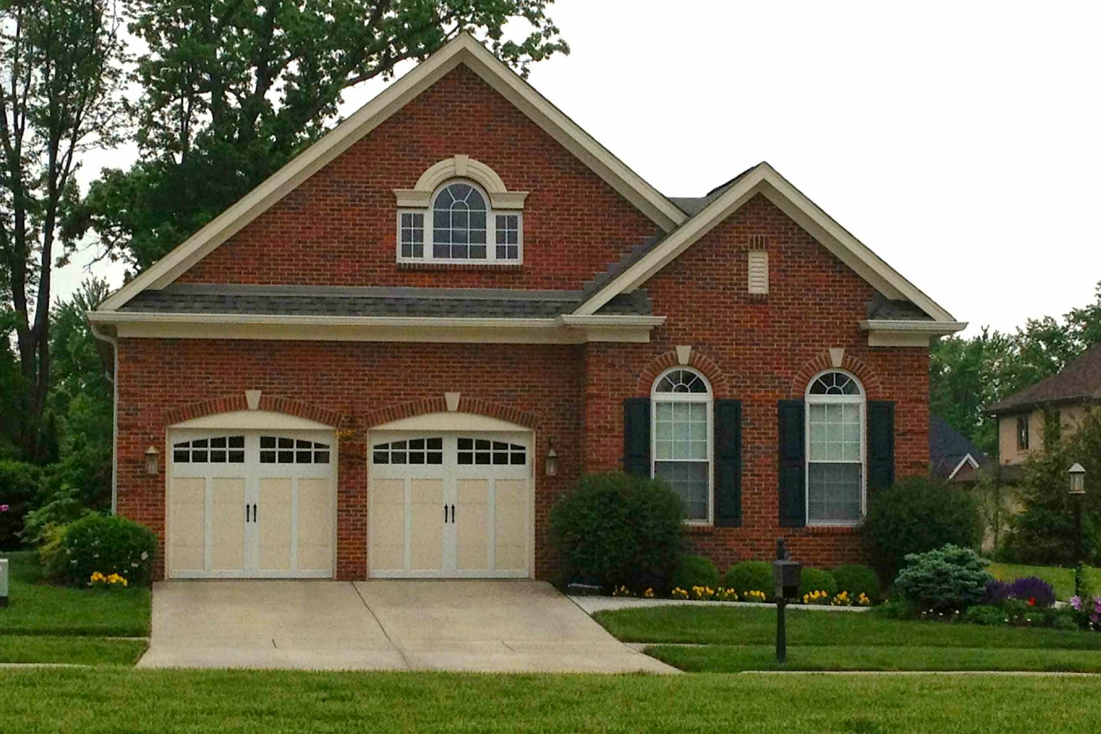 The arched shape of these garage doors\u0027 window openings and the ision of the windows with square grilles mimic the design of the arched windows to the ... & Garage Door Replacement: 10 Tips for Making the Right Choice ... Pezcame.Com