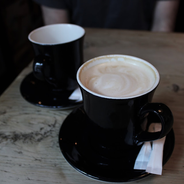 Two coffees in black mugs