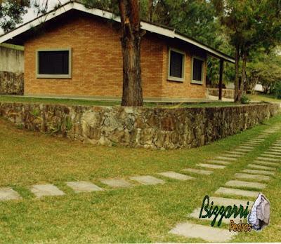 Muro de pedra com pedra moledo com a casa de tijolo a vista, o gramado com grama São Carlos e os caminhos do carro com pedra com junta de grama.