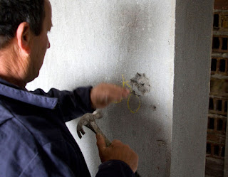 Bekir chiseling out a light switch location