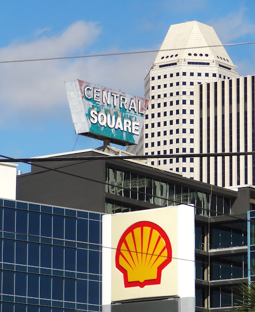 Shell Logo at gas station in Midtown with Central Square signage behind and Cullen Center  Office Towers