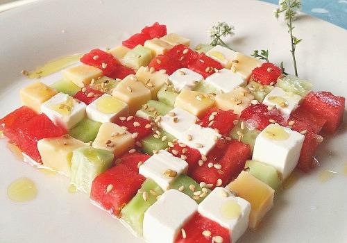 Una ensalada multicolor con queso feta,  queso gouda, pepino y sandia