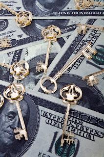 Gold keys on top of hundred dollar bills