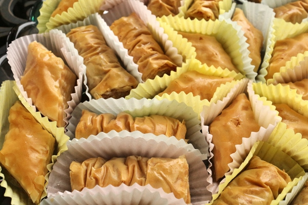 Tray of assorted baklava and bourma baklava pastries served in paper cupcake liners