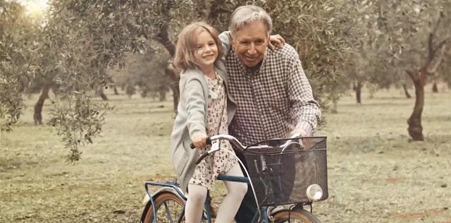 Un abuelo y su nieta disfrutando de un paseo en bici a través de los olivos