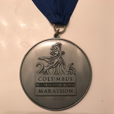 "2006 Columbus Marathon medal; I know that times and slogans change, but I loved  ""Our World is Flat"""