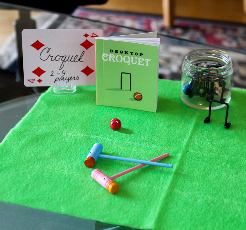 Mini croquet game with painted pieces to look like flamingos and hedgehogs