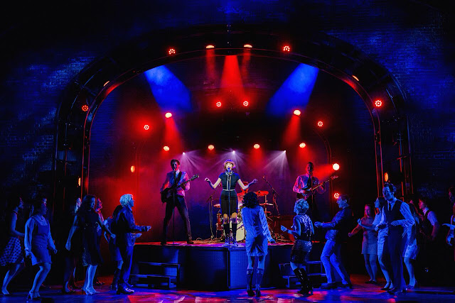 kara lily hayworth as cilla black singing on the cavern stage with the beatles behind her and a crowd dancing in front