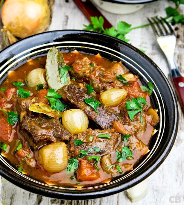 Recept Stifado, een kruidige Griekse runderstoofpot met tomaat en zilveruitjes
