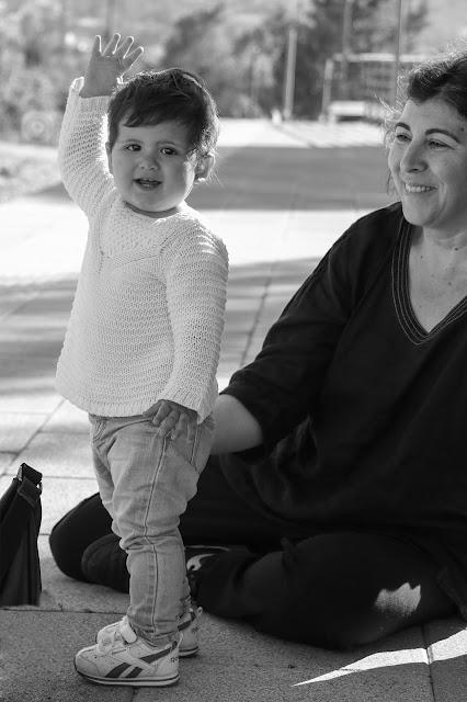 Sofía (1 año) con la mano levantada saludando al lado de su madre.