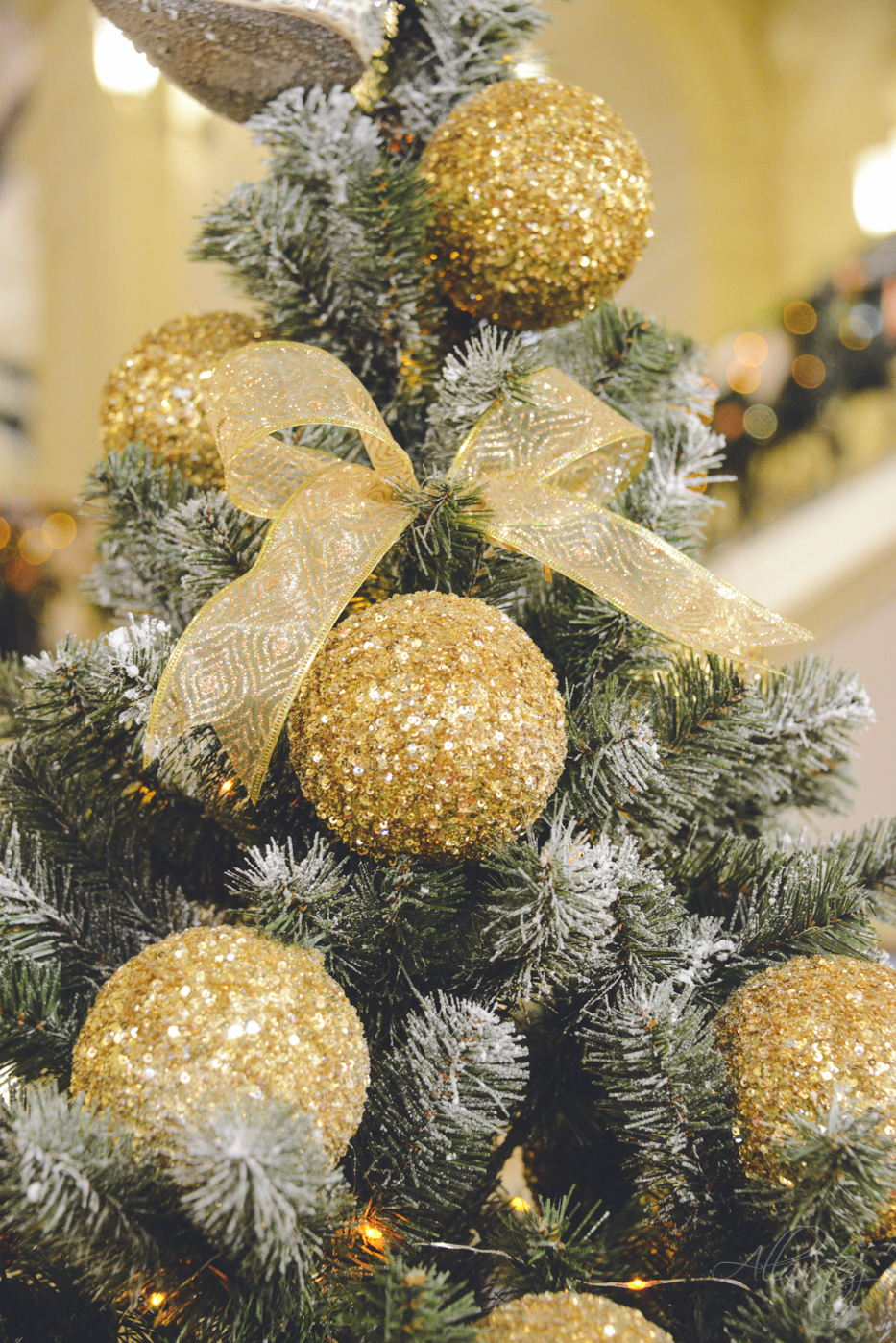 designer Christmas tree decorated with golden glitter Christmas balls and bow ribbons