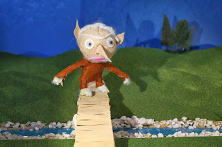 Photograph of finished troll model standing on bridge in green, hilly set.