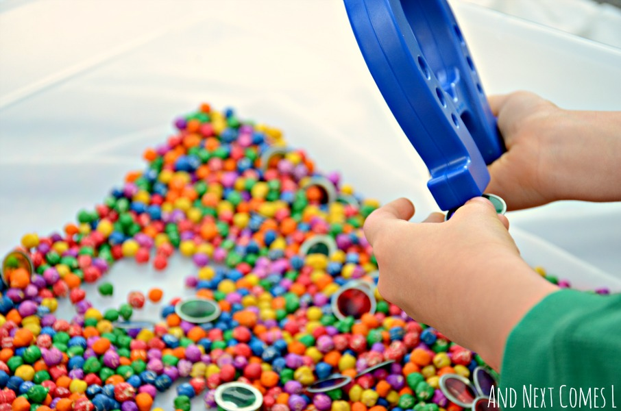Exploring magnets in a colorful sensory bin from And Next Comes LMagnets and rainbow dyed chickpeas sensory play for toddlers and preschoolers from And Next Comes L
