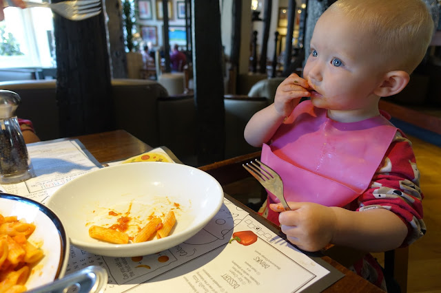 A toddler with a pink bib on sitting in a highchair in Prezzo eating pasta