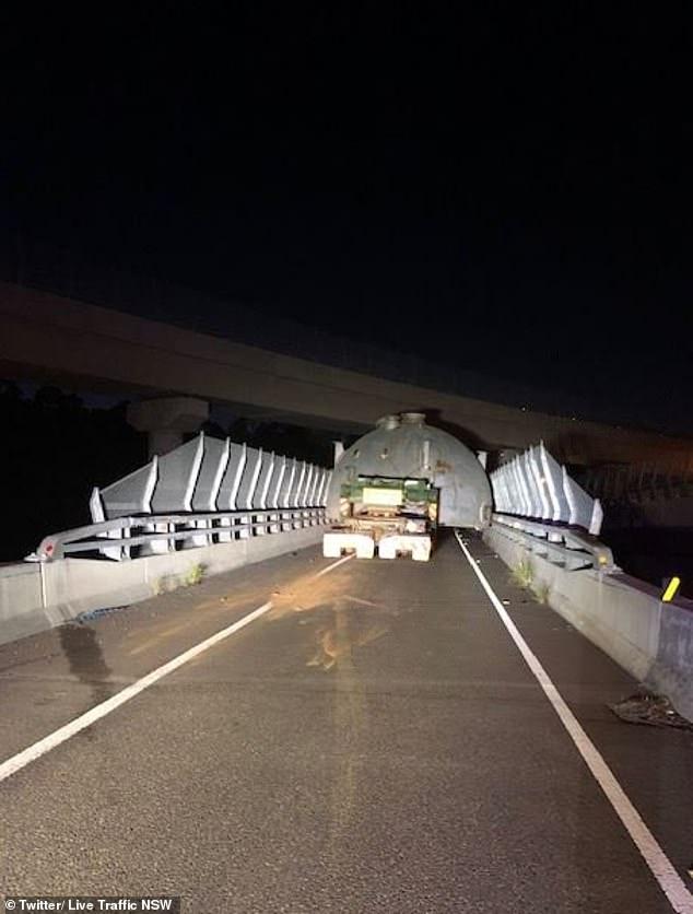 Tension as huge truck gets stuck under a low bridge causing massive traffic