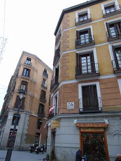 Lla placa de cerámica con el nombre de la calle en la esquina de un típico edificio con planta baja de granito y plantas superiores de color ocre con balcones enmarcados en blanco.