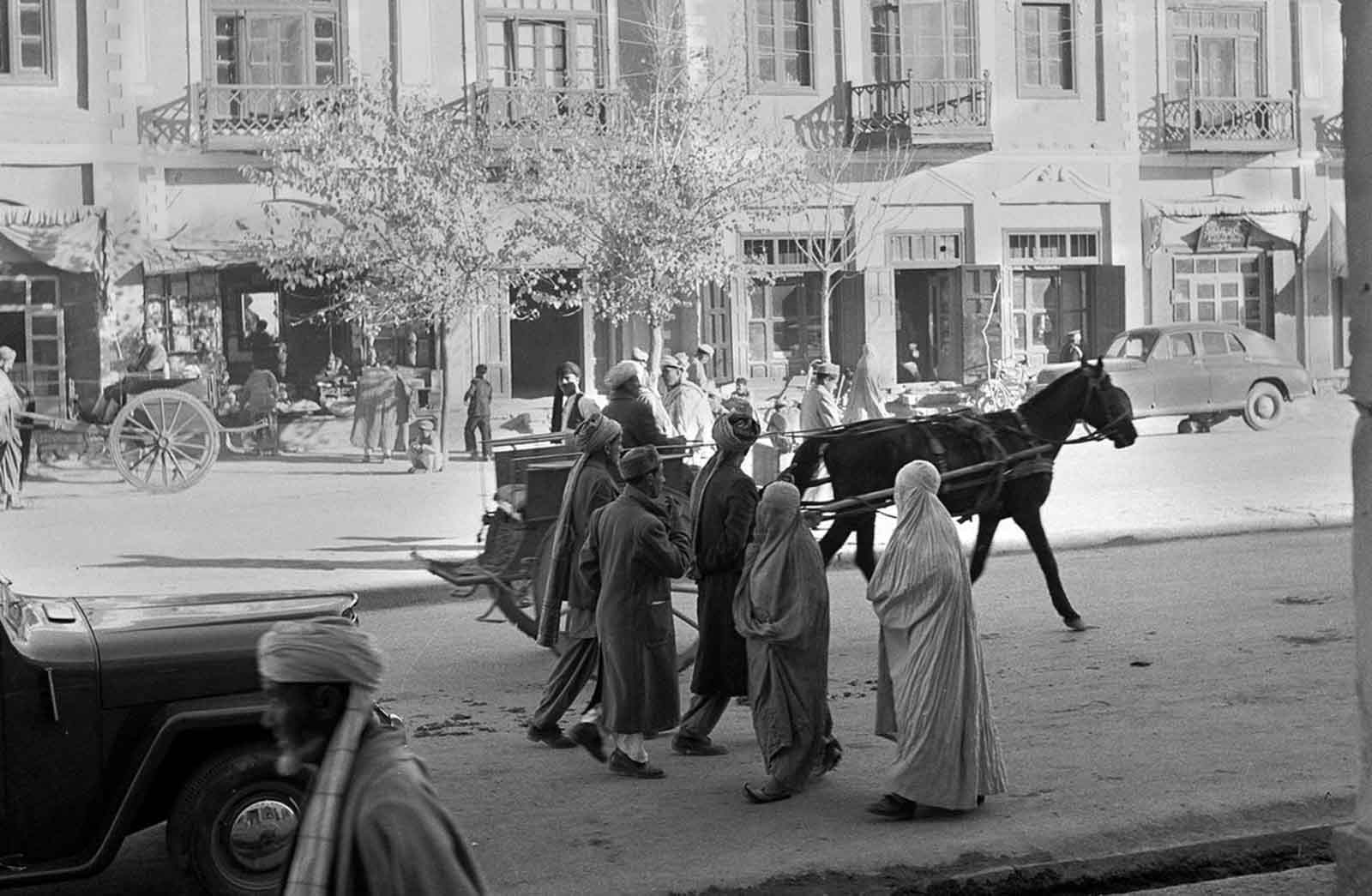 Women, wearing traditional burqas and Persian slippers, walk alongside men, cars and horse carts, in a street in Kabul, in 1951. At the time, this street was one of only three paved streets in the capital city.