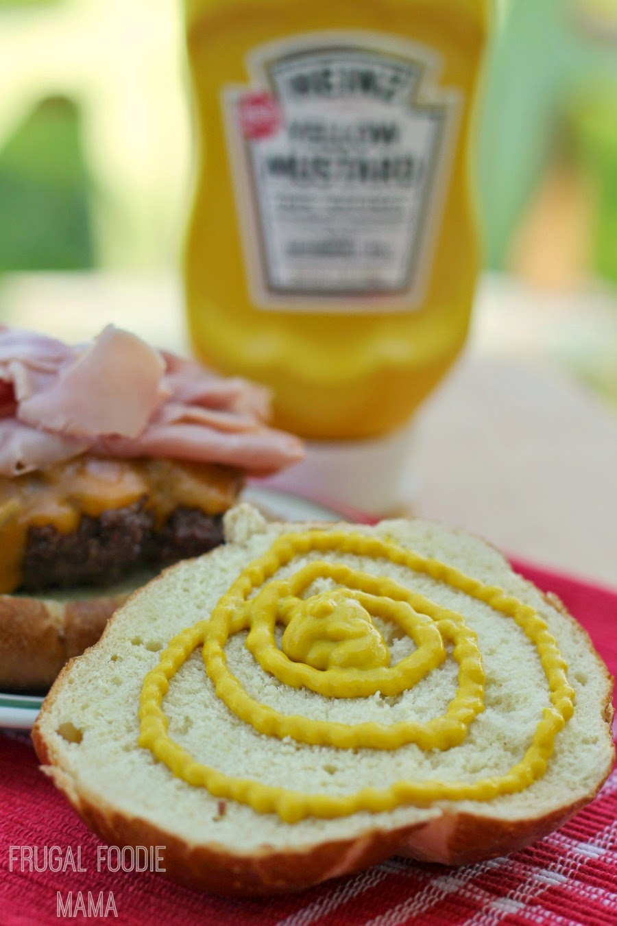 A juicy burger is topped with ham, cheddar cheese, & Heinz Yellow Mustard on a pretzel bun in this crowd-pleasing Bavarian Ham Burger.